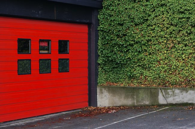 A red sectional garage door with windows